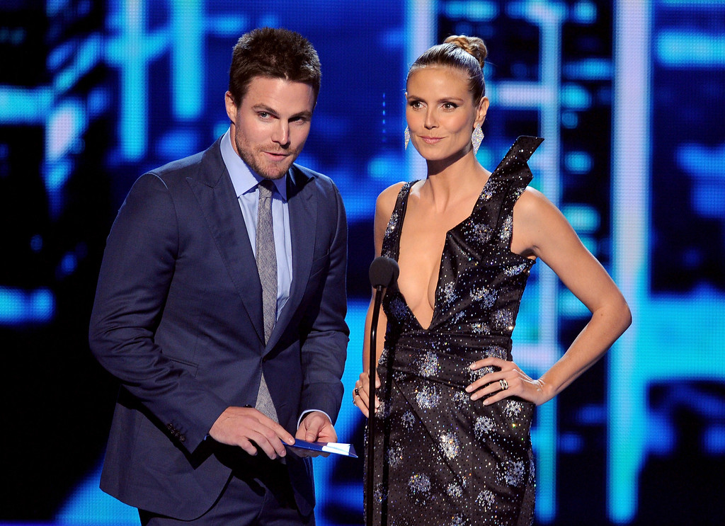 Description of . LOS ANGELES, CA - JANUARY 08:  Actor Stephen Amell (L) and TV personality Heidi Klum speak onstage at The 40th Annual People's Choice Awards at Nokia Theatre L.A. Live on January 8, 2014 in Los Angeles, California.  (Photo by Kevin Winter/Getty Images)