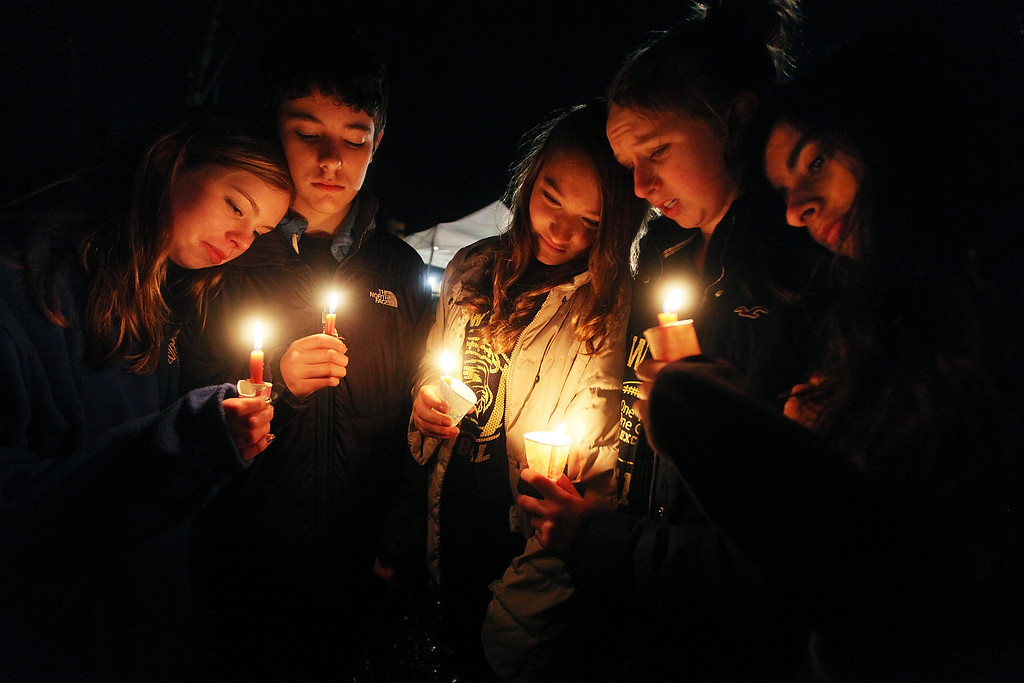 Description of . NEWTOWN, CT - DECEMBER 16:  (L to R) Newtown residents Claire Swanson, Ian Fuchs, Kate Suba, Jaden Albrecht, Simran Chand hold candles at a memorial for victims on the first Sunday following the mass shooting at Sandy Hook Elementary School on December 16, 2012 in Newtown, Connecticut. U.S. President Barack Obama visited the grief stricken town today.  (Photo by Mario Tama/Getty Images)