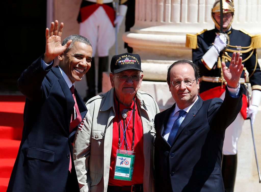 Description of . U.S. President Barack Obama, left, and French President Francois Hollande, right, waves with World War II veteran Kenneth