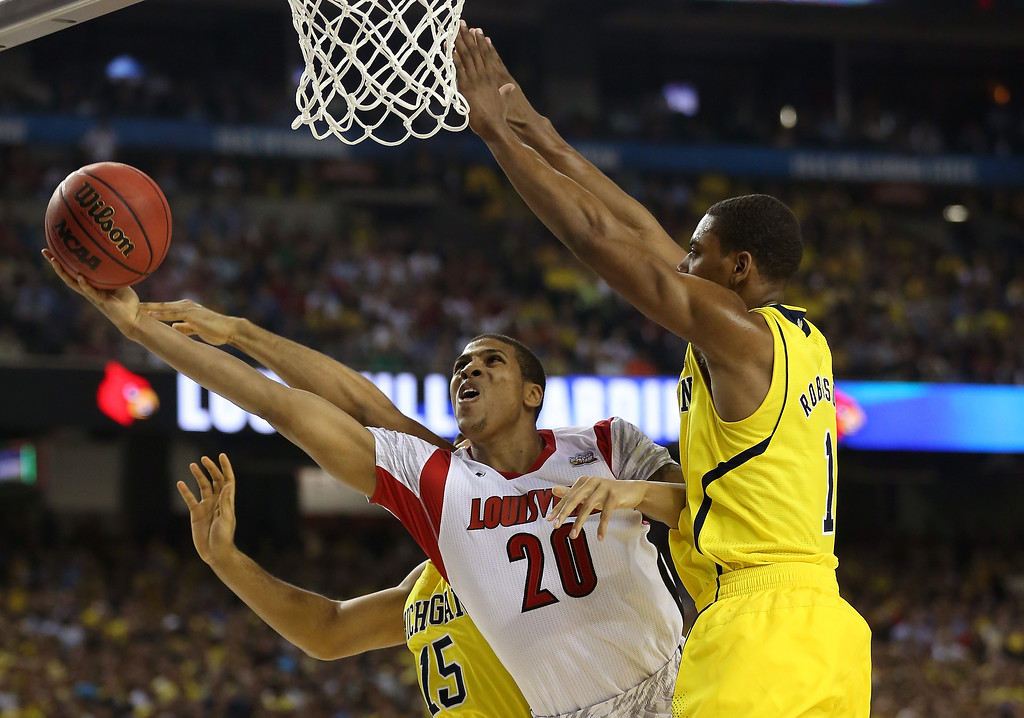 Description of . Wayne Blackshear #20 of the Louisville Cardinals attempts a shot in the second half against Jon Horford #15 and Glenn Robinson III (R) #1 of the Michigan Wolverines during the 2013 NCAA Men\'s Final Four Championship at the Georgia Dome on April 8, 2013 in Atlanta, Georgia.  (Photo by Streeter Lecka/Getty Images)