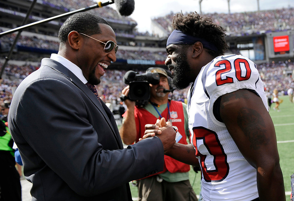 Description of . Former Baltimore Ravens linebacker Ray Lewis, left, and Houston Texans free safety Ed Reed chat during halftime of an NFL football game between the Ravens and the Texans Sunday, Sept. 22, 2013, in Baltimore. (AP Photo/Nick Wass)