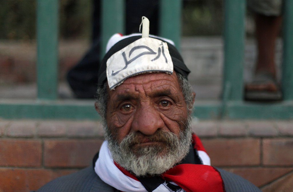 Description of . An Egyptian protester wears a head band with Arabic writing that reads,