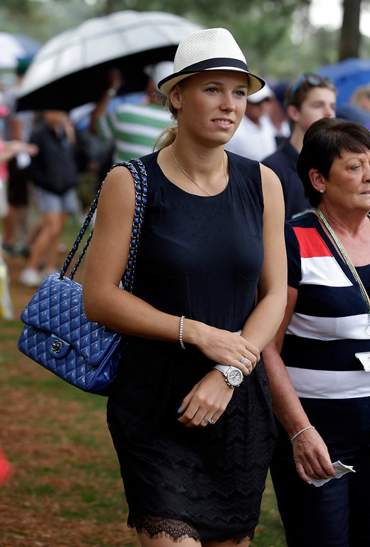 Description of . Tennis player Caroline Wozniacki follows Rory McIlroy, of Northern Ireland, during his second round of the Masters golf tournament Friday, April 12, 2013, in Augusta, Ga. (AP Photo/Darron Cummings)