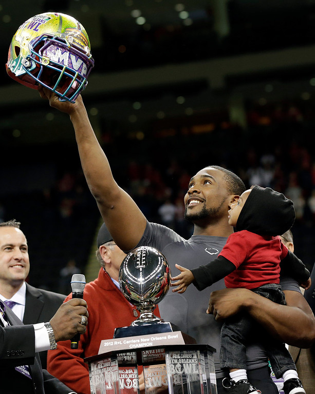 Description of . Louisiana-Lafayette quarterback Terrance Broadway (8) holds his son Terrance and the New Orleans Bowl helmet after defeating East Carolina in the New Orleans Bowl NCAA college football game in New Orleans on Saturday, Dec. 22, 2012. Louisiana-Lafayette defeated East Carolina 43-34. (AP Photo/Skip Martin)