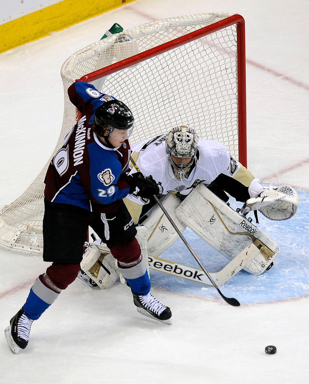 Description of . Colorado Avalanche center Nathan MacKinnon tries to score on Pittsburgh Penguins goalie Marc-Andre Fleury during the first period of an NHL hockey game Sunday, April 6, 2014, in Denver. (AP Photo/Chris Schneider)