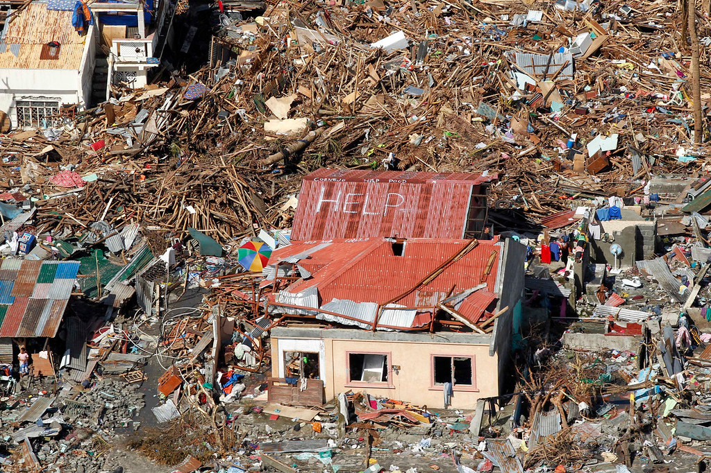 Description of . An aerial view shows signs for help and food amid the destruction left from Typhoon Haiyan in the coastal town of Tanawan, central Philippines, Wednesday, Nov. 13, 2013. Typhoon Haiyan, one of the strongest storms on record, slammed into six central Philippine islands on Friday leaving a wide swath of destruction and thousands of people dead. (AP Photo/Wally Santana)