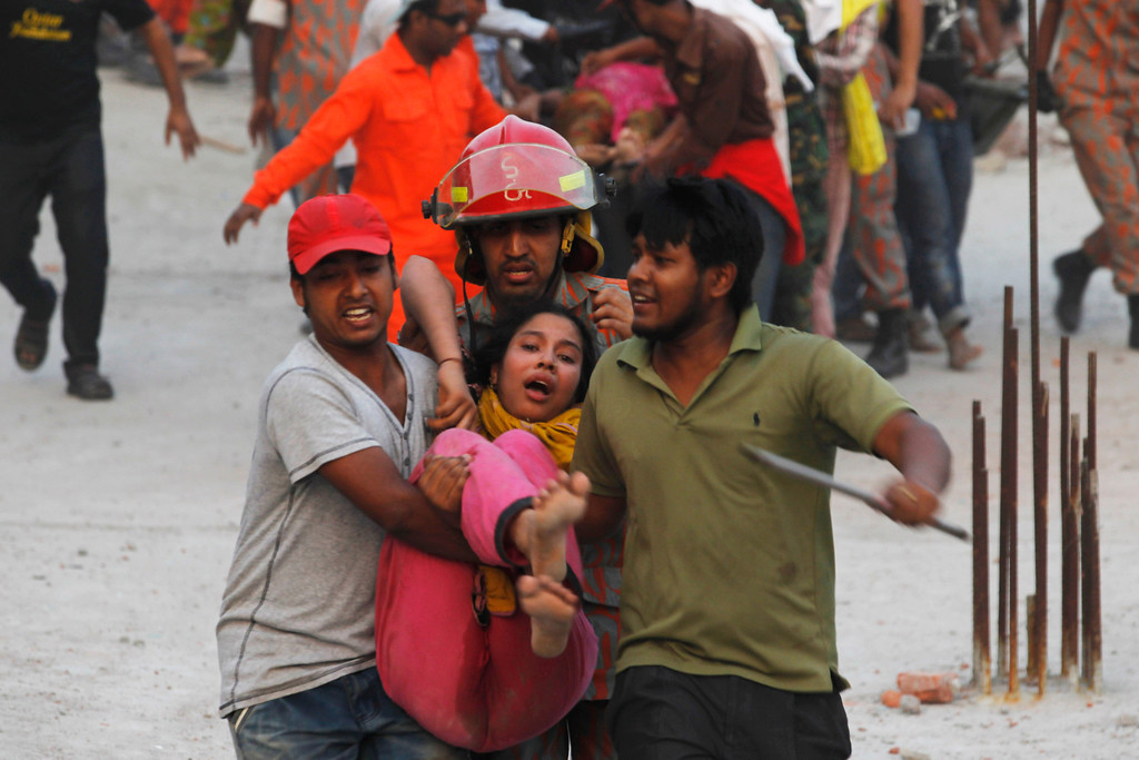Description of . Rescue workers carry a garment worker who was trapped inside the rubble of the Rana Plaza building which collapsed, in Savar, 30 km (19 miles) outside Dhaka April 24, 2013. REUTERS/Andrew Biraj