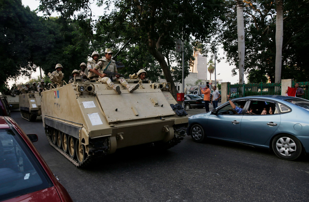 Description of . People flash peace sign at Egyptian soldiers riding on armored personnel carriers on their way to Tahrir Square in Cairo Friday, July 5, 2013. An umbrella group of opponents of Egypt's ousted President Mohammed Morsi called the public to join rallies immediately to counter a