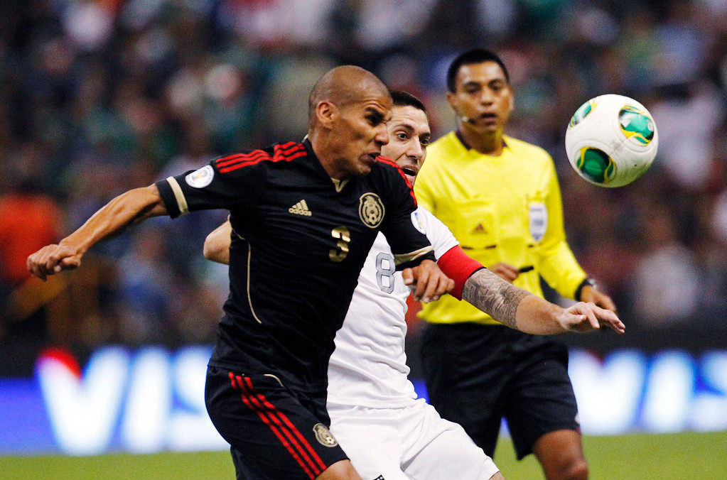 Description of . Mexico's Carlos Salcido (L) fights for the ball with Clint Dempsey of the U.S. during their 2014 World Cup qualifying soccer match at Azteca stadium in Mexico City, March 26, 2013. REUTERS/Edgard Garrido