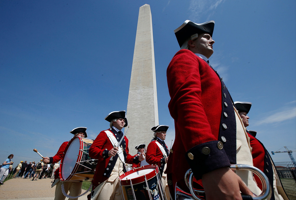 . Members of the United States Army Old Guard Fife and Drums Corps march beneath the Washington Monument in Washington, Monday, May 12, 2014, during a ceremony to celebrate its re-opening.  (AP Photo)