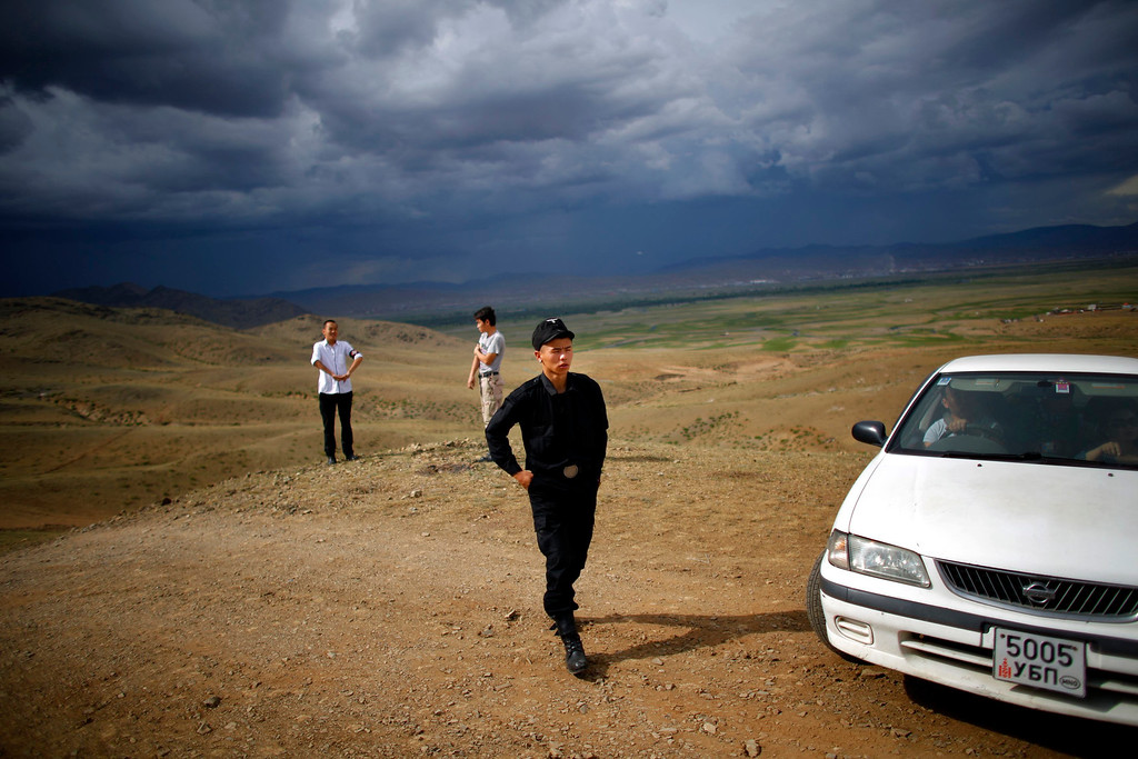 Description of . Members of the Mongolian neo-Nazi group Tsagaan Khass take a break as they travel to a quarry, where they questioned a worker, southwest of Ulan Bator June 23, 2013. The group has rebranded itself as an environmentalist organisation fighting pollution by foreign-owned mines, seeking legitimacy as it sends Swastika-wearing members to check mining permits. Over the past years, ultra-nationalist groups have expanded in the country and among those garnering attention is Tsagaan Khass, which has recently shifted its focus from activities such as attacks on women it accuses of consorting with foreign men to environmental issues, with the stated goal of protecting Mongolia from foreign mining interests. This ultra-nationalist group was founded in the 1990s and currently has 100-plus members. Picture taken June 23, 2013. REUTERS/Carlos Barria