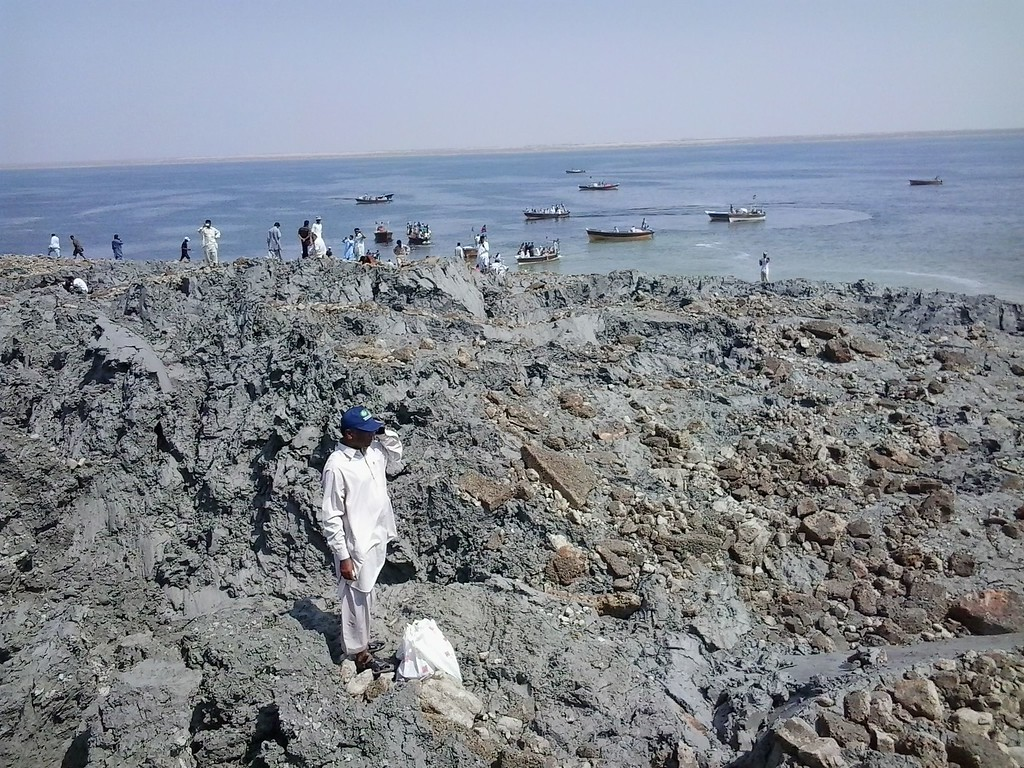 Description of . This photograph taken on September 25, 2013, shows Pakistani residents as they gather on an island that appeared some two kilometres off the coastline of Gwadar after an earthquake. AFP PHOTO / Behram  BALOCH/AFP/Getty Images
