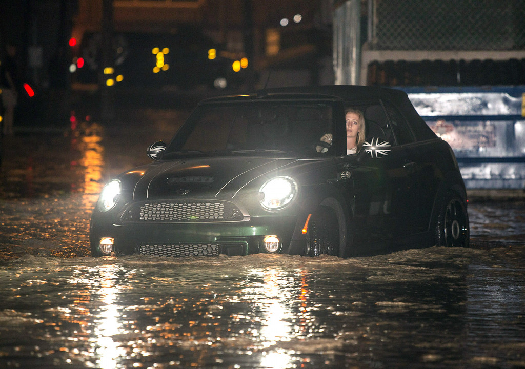 Description of . In this Tuesday, Aug. 26, 2014 photo, a woman drives through a flooded street after high tide and large waves caused heavy flooding in Seal Beach, Calif.  (AP Photo/Kevin Warn)
