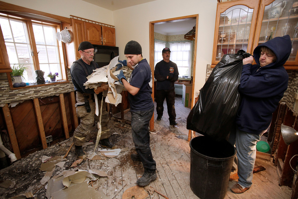 Description of . New Orleans firefighter Bruce Hurley, Sr., left, and New York firefighter John Militano, clear sheetrock from a gutted kitchen as homeowner Colleen Dwyer, right, bags debris in her home flooded in Superstorm Sandy in the Belle Harbor section of Queens, N.Y., Wednesday, Nov. 28, 2012. The New Orleans Fire Department is returning the help given to Louisiana after Hurricane Katrina by firefighters and other emergency workers from New York. (AP Photo/Mark Lennihan)