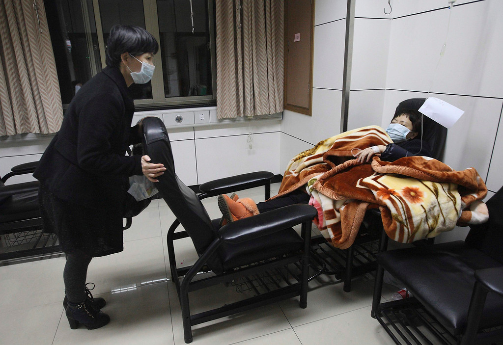 Description of . A patient with fever (R) is accompanied by a family member while receiving treatment at the hospital where a 67-year-old H7N9 patient is being treated, in Hangzhou, Zhejiang province, April 3, 2013. China said it was mobilising resources nationwide to combat a new strain of deadly bird flu that has killed three people, as Japan and Hong Kong stepped up vigilance against the virus and Vietnam banned imports of Chinese poultry. A total of 10 people in China have been confirmed to have contracted H7N9, all in the east of the country. The latest was a 64-year-old man from Huzhou in the eastern province of Zhejiang, who state media said on Thursday was admitted to hospital on March 31. Picture taken April 3, 2013. REUTERS/Chance Chan