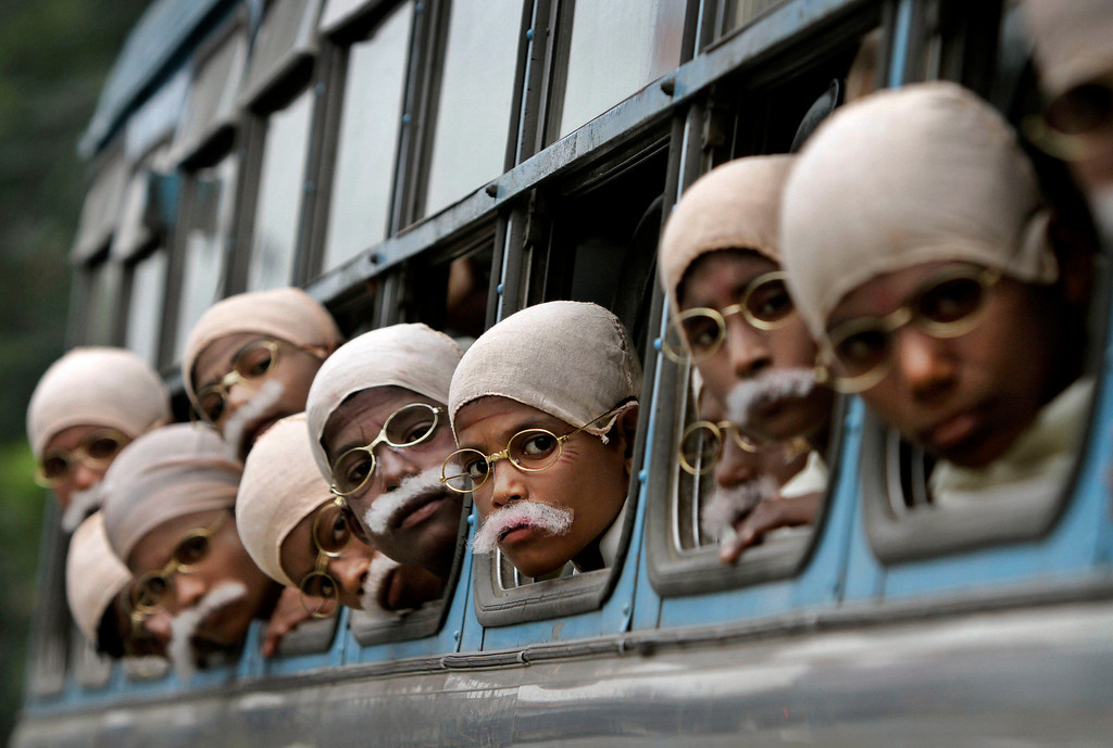 Description of . In this Jan. 29, 2012 file photo, underprivileged Indian children dressed in costume to look like the late Mahatma Gandhi arrive on a  bus before attempting a world record in Kolkata, India. Local non-government organizations put on the event and a total of 485 children took part in the rally ahead of the anniversary of Gandhi's death which falls on January 30th. (AP Photo/Bikas Das, File)