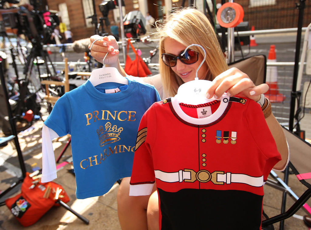 Description of . A member of the U.S. media decides which baby clothes to show to the camera outside the Lindo Wing of St Mary\'s Hospital, where Britain\'s Catherine, Duchess of Cambridge is due to give birth, in London July 15, 2013. The first child of Prince William and his wife Kate is due in mid-July, with the couple saying they have no idea of the sex of the baby, who will be third in line to the British throne.  REUTERS/Olivia Harris