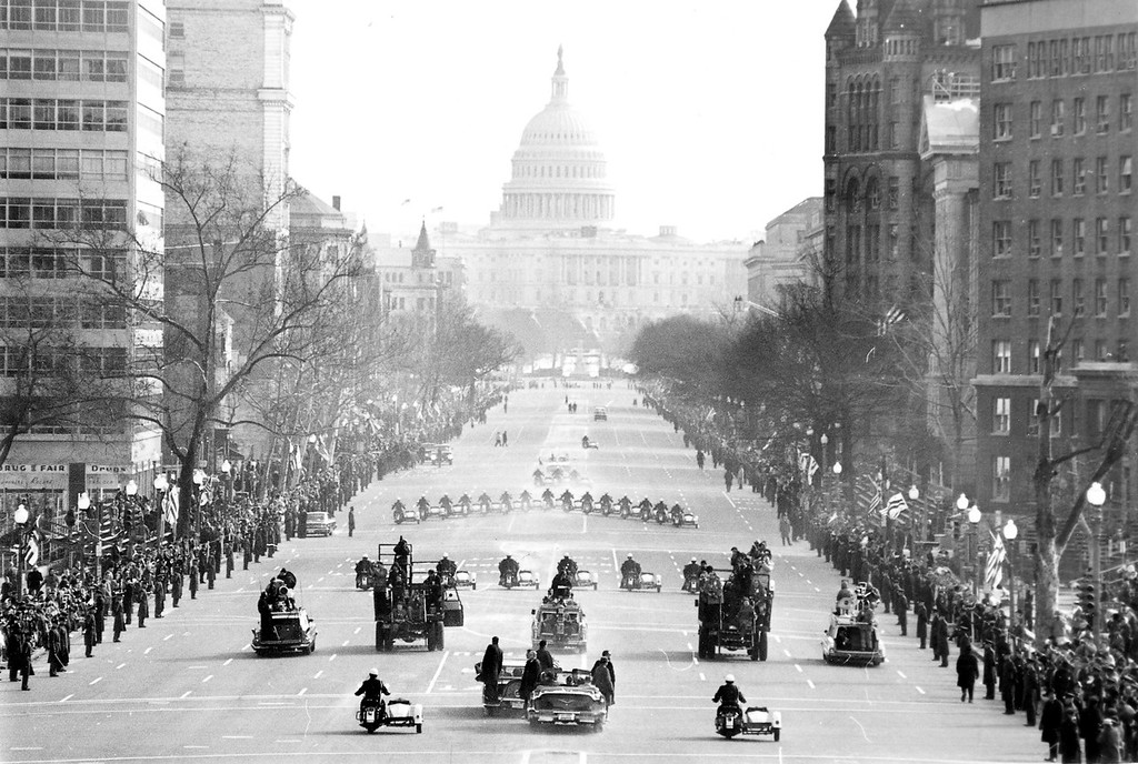 Description of . The motorcade bringing President Johnson to the Capitol for his inauguration moves along Pennsylvania Avenue, January 20, 1965.  Police on motorcycles lead the way. Johnson is in a closed car at lower center with Secret Service agents on the bumper. Another car full of Secret Service men is close by. (AP Photo)