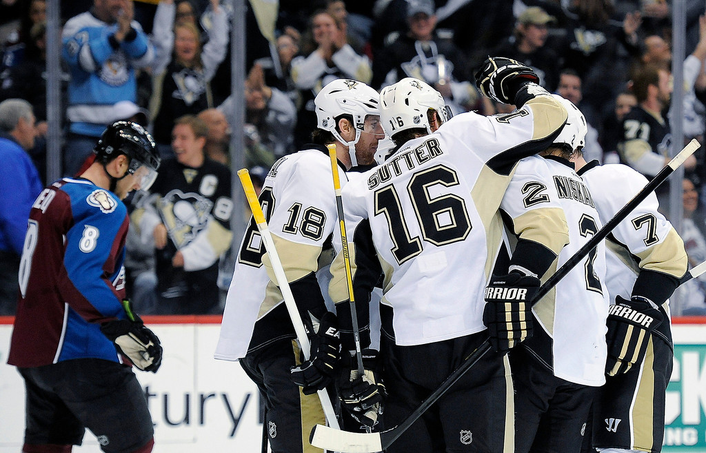 Description of . The Pittsburgh Penguins celebrate a goal by Brandon Sutter during the second period of an NHL hockey game against the Colorado Avalanche on Sunday, April 6, 2014, in Denver. The Penguins won in a shootout, 3-2. (AP Photo/Chris Schneider)