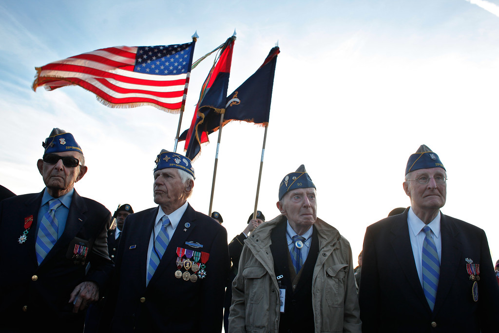 Description of . From left, World War II veterans of the U.S. 29th Infantry Division, Hal Baumgarten, 90 from Pennsylvania, Steve Melnikoff, 94, from Maryland, Don McCarthy, 90 from Rhode Island, and Morley Piper, 90, from Massachusetts, attend a D-Day commemoration, on Omaha Beach, western France , (AP Photo/Thibault Camus)
