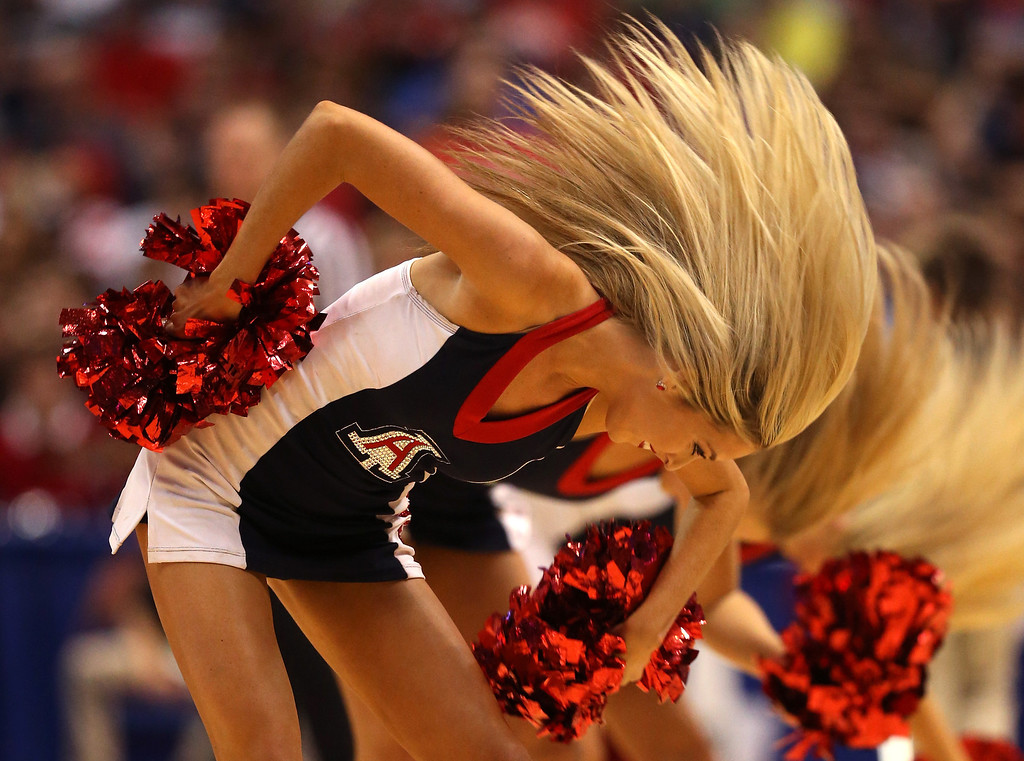 Description of . An Arizona Wildcats cheerleader performs as the Wildcats take on the Wisconsin Badgers during the West Regional Final of the 2014 NCAA Men's Basketball Tournament at the Honda Center on March 29, 2014 in Anaheim, California.  (Photo by Jeff Gross/Getty Images)