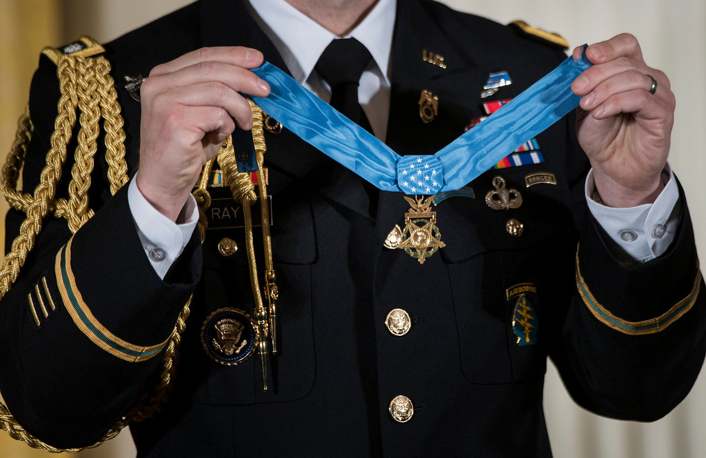 Description of . A military aid holds the Medal of Honor during a ceremony in the East Room of the White House February 11, 2013 in Washington, DC. Former US Army Staff Sargent Clinton Romesha was awarded the Medal of Honor by US President Barack Obama for his gallantry during an insurgent attack on Combat Outpost Keating in Afghanistan in 2009. AFP PHOTO/Brendan  SMIALOWSKI/AFP/Getty Images