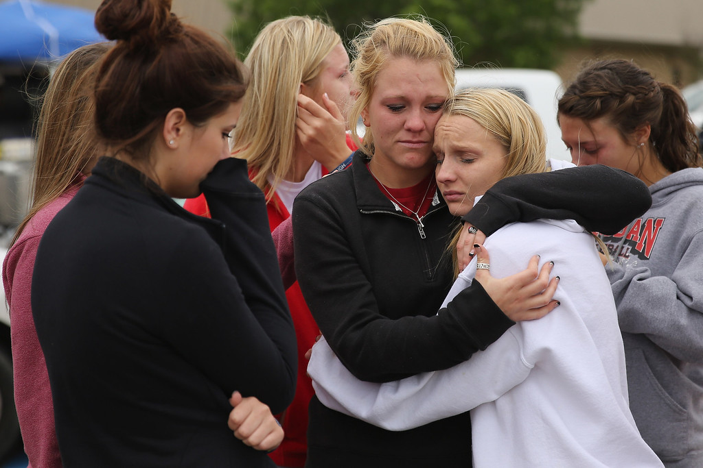 Description of . WEST, TX - APRIL 18:  West High School senior students Kelsey Hoelscher (C) and Heather Perry (R) embrace after praying for the victims and survivors the day after the West Fertilizer Company explosion April 18, 2013 in West, Texas. Hoelscher's uncles, Bob Snokhous and Doug Snokhous, were volunteer fire fighters who are presumed dead after the fertilizer company caught fire and exploded, injuring more than 160 people and leaving damaged buildings for blocks in every direction. (Photo by Chip Somodevilla/Getty Images)  *** BESTPIX ***