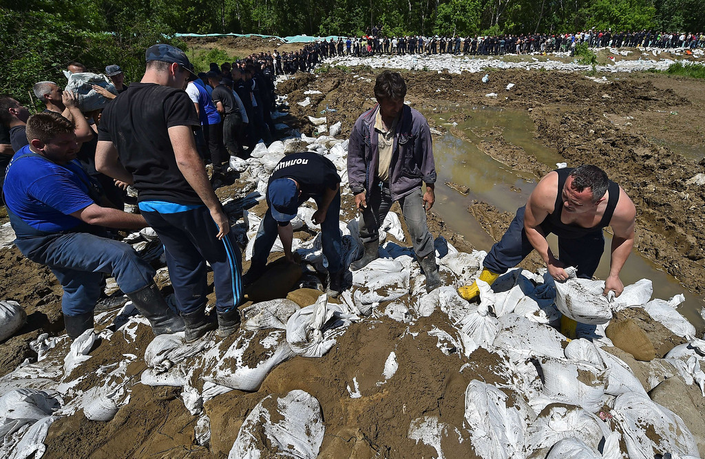 Description of . Volunteers and police officers pass sandbags to reinforce the bank of the river Sava near Sabac, 100 kilometers west of Belgrade, on May 19, 2014. The Balkans braced for more misery as the death toll from the worst floods in a century rose to 47 and rising waters forced thousands more to flee their homes. Muddy waters from the Sava River have submerged houses, churches, mosques and roads in Bosnia, Serbia and Croatia after record rainfall wreaked havoc across the central European region. AFP PHOTO / ANDREJ ISAKOVIC/AFP/Getty Images