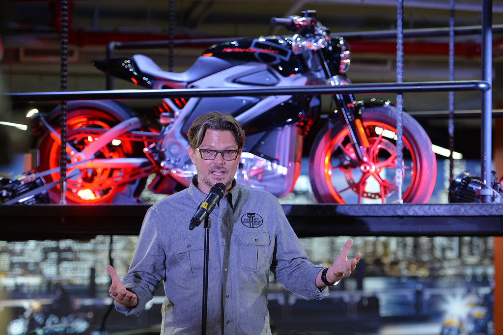 Description of . Harley-Davidson chief marketing officer Mark-Hans Richer, speaks in front of a Project LiveWire motorcycle, the company's first electric motorcycle, during a preview June 23, 2014 at a Harley-Davidson dealer in New York. AFP PHOTO/Stan HONDA/AFP/Getty Images