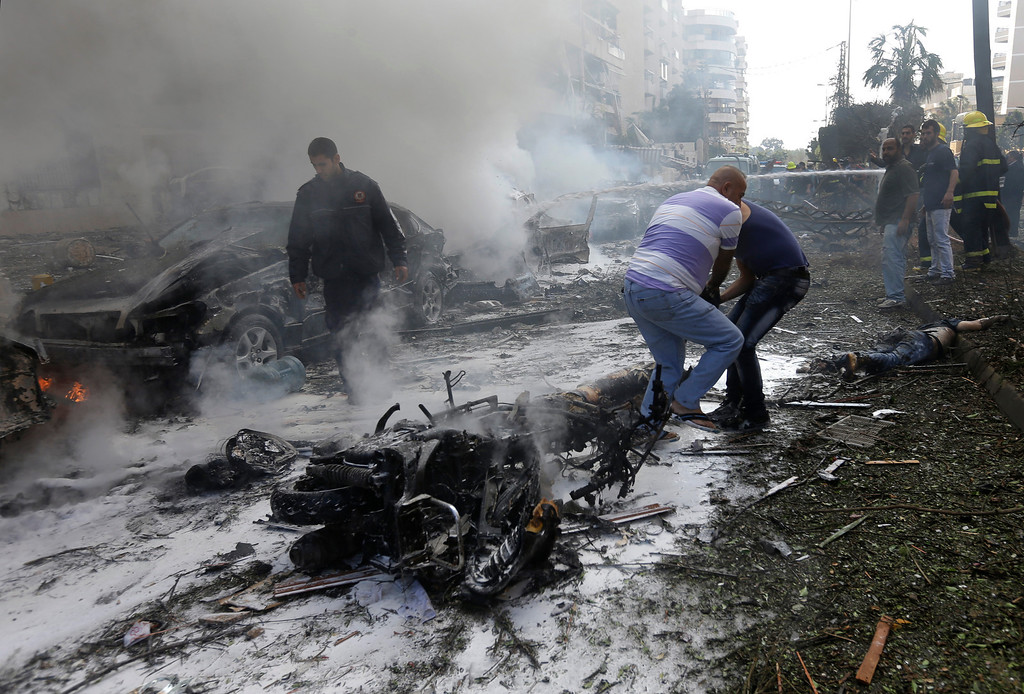 Description of . Lebanese men remove a dead body from the ground in front of burned cars, at the scene where two explosions have struck near the Iranian Embassy killing many, in Beirut, Lebanon, Tuesday Nov. 19, 2013. (AP Photo/Hussein Malla)