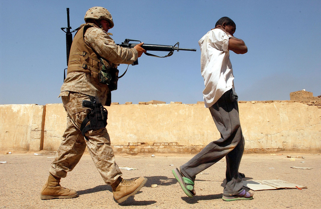 Description of . A U.S. Marine takes away a man suspected of looting April 14, 2003 in Baghdad, Iraq. The Marines began to crack down on looters after Baghdad residents complained of the lack of law and order in the capital. (Photo by Spencer Platt/Getty Images)