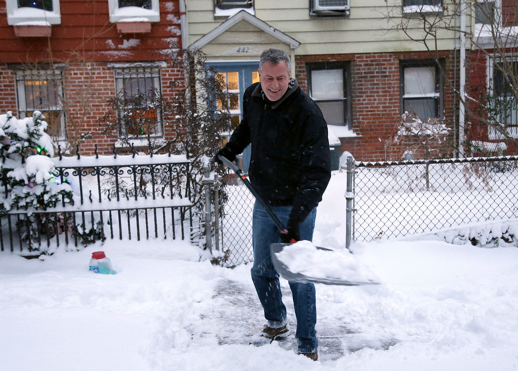 Description of . In this Jan. 3, 2014 file photo, New York City Mayor Bill de Blasio shovels the sidewalk in front of his house in New York. With less than 36 hours into his tenure, the first test of the new mayor's leadership skills arrived in the form of a major winter storm.  (AP Photo/Seth Wenig, File)