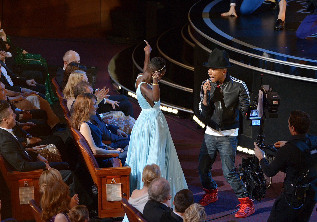 Description of . Lupita Nyong'o, left, dances along with Pharrell Williams during his performance of