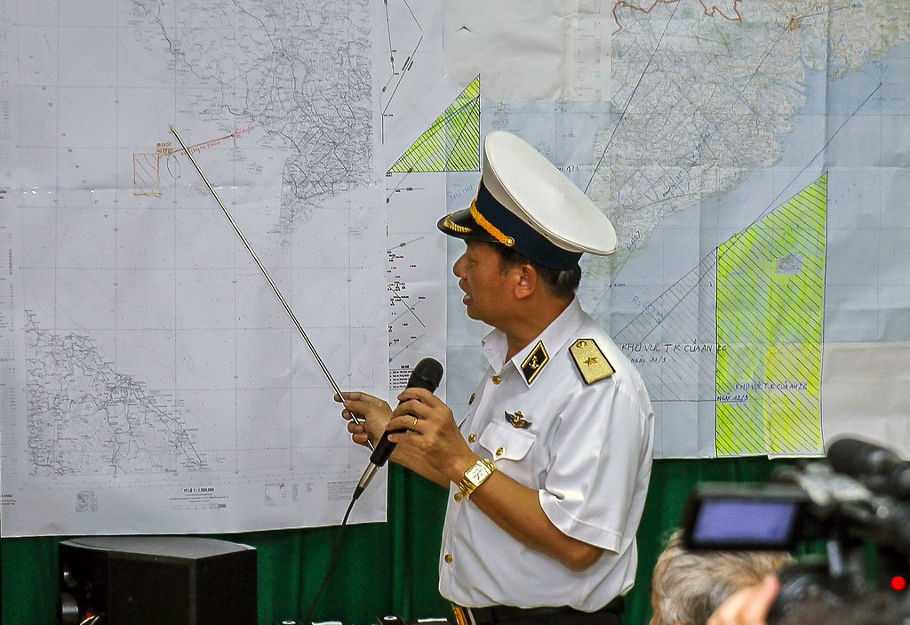 Description of . Vietnamese Navy's Deputy Commander Rear Admiral Le Minh Thanh (R) points at a map to show the area where Vietnam is conducting search activities for the missing Malaysia Airlines flight 370 in Phu Quoc island on March 12, 2014. Vietnam said on March 12 it had suspended its air search for missing flight MH370 and scaled back a sea search as it waited for Malaysia to clarify the potential new direction of the multi-national hunt.        AFP PHOTO / LE QUANG NHAT/AFP/Getty Images