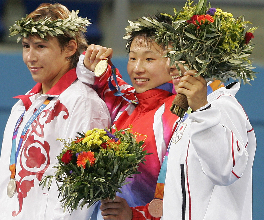 Description of . Chinese wrestler Wang Xu (C), gold, Russian Gouzel Maniourova (L), silver, and Japanese Hamaguchi Kyoko pose on the podium after winning the women's 72KG wrestling final, at the Ano Liossia stadium at the 2004 Olympic Games, 23 August 2004 in Athens.  ANTONIO SCORZA/AFP/Getty Images