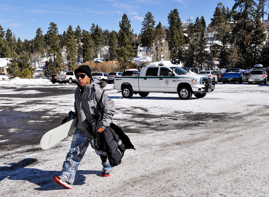 Description of . Rod Guzman, 25, of San Clemente, makes his way towards the Bear Mountain slopes while one lone law enforcement vehicle remains in parking lot that once housed the command post for the Christopher Dorner manhunt in Big Bear on Sunday, Feb. 10, 2013. Search crews were reduced 25 personnel on Sunday from 50 the day before, and the parking lot was reopened to skiers and snowboarders.(Rachel Luna / Staff Photographer)