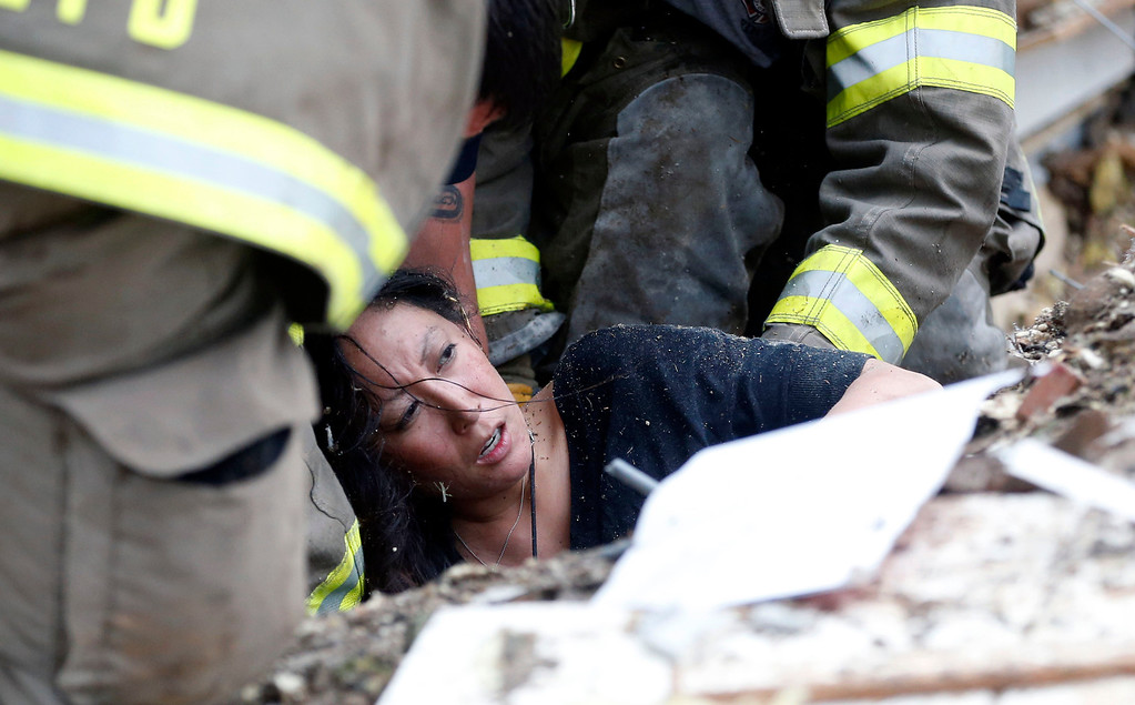 Description of . In this May 20, 2013, file photo, Jennifer Doan, a teacher at Plaza Towers Elementary School, is pulled out from under tornado debris at the school in Moore, Okla. (AP Photo/Sue Ogrocki, File)
