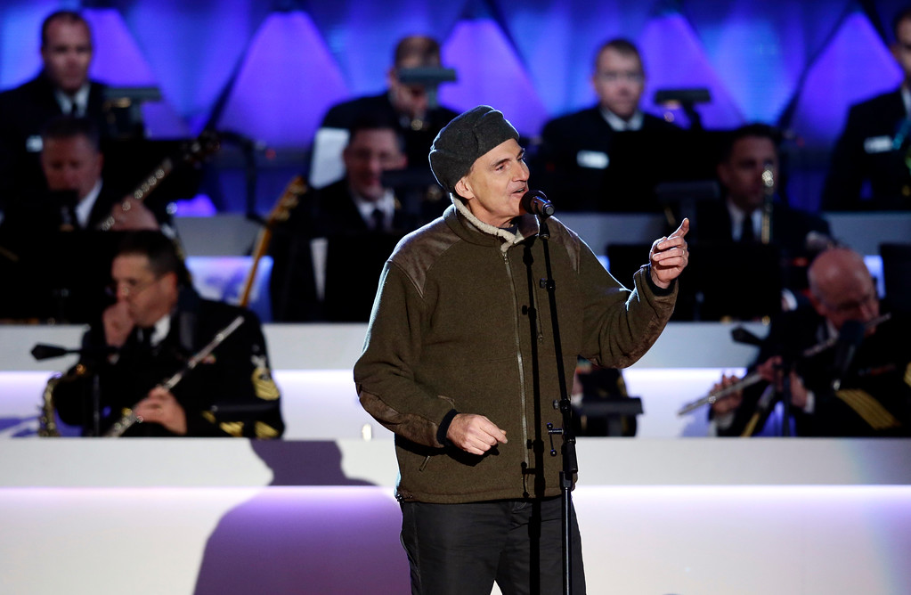 Description of . Performer James Taylor sings during the 90th annual National Christmas Tree Lighting ceremony on the Ellipse south of the White House, Thursday, Dec. 6, 2012 in Washington. (AP Photo/Alex Brandon)