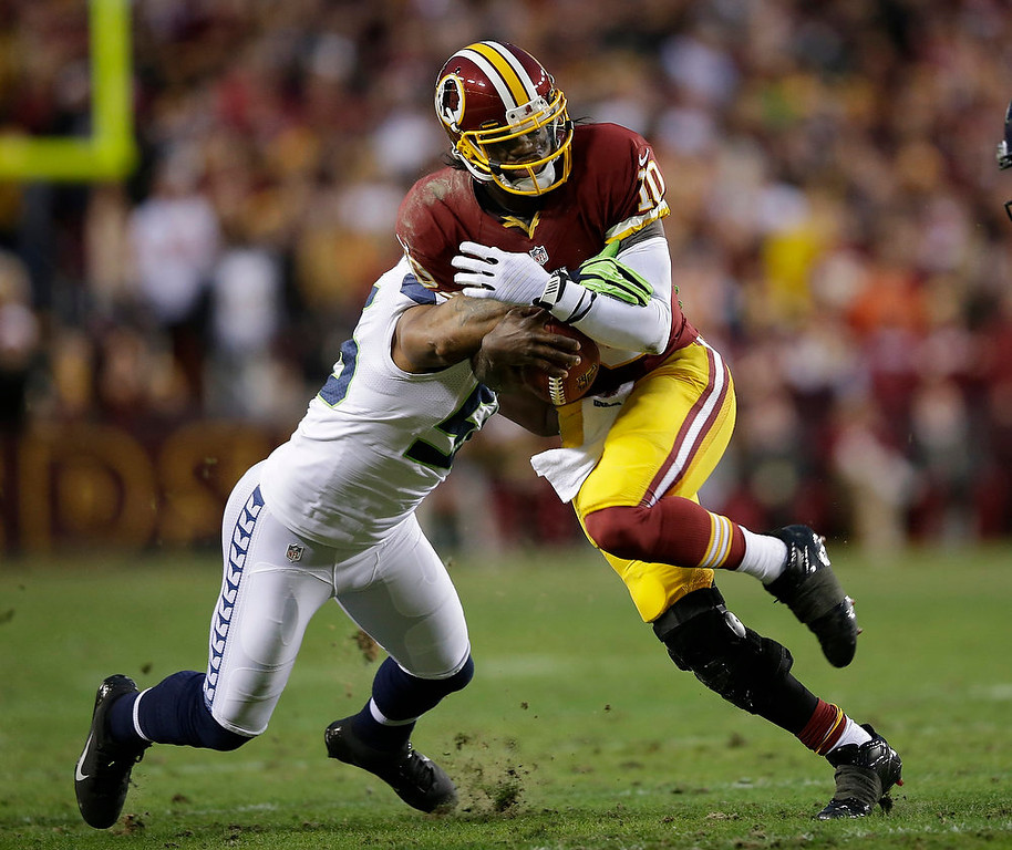 Description of . Seattle Seahawks outside linebacker Leroy Hill stops Washington Redskins quarterback Robert Griffin III during the first half of an NFL wild card playoff football game in Landover, Md., Sunday, Jan. 6, 2013. (AP Photo/Evan Vucci)