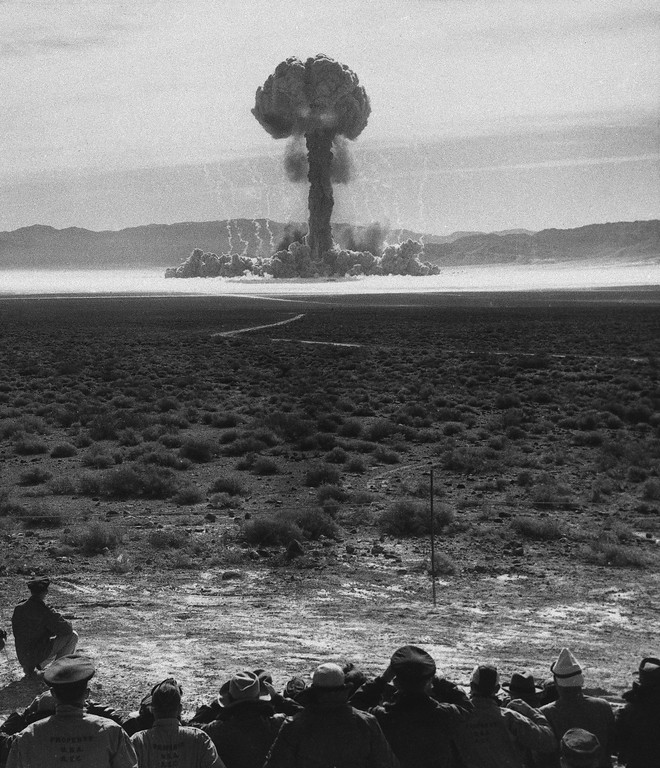 Description of . Official military observers and U.S. congressmen watch the mushroom cloud form on Frenchman flag, a moment after history's first atomic artillery shell was fired in Las Vegas, Nev., May 25, 1953.  Among the observers are Secretary Defense Charles E. Wilson and Admiral Arthur W. Radford, new Chairman of the Joint Chiefs of Staff.  (AP Photo/Department of Defense)
