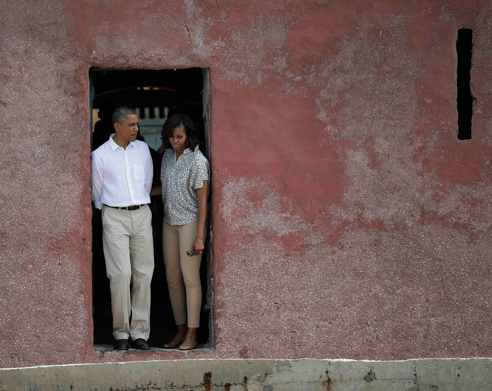 Description of . U.S. President Barack Obama and first lady Michelle Obama look out of a doorway that slaves departed from on Goree Island in Dakar June 27, 2013. Obama's trip, his second to the continent as president, will take him to Senegal, South Africa and Tanzania.  REUTERS/Gary Cameron