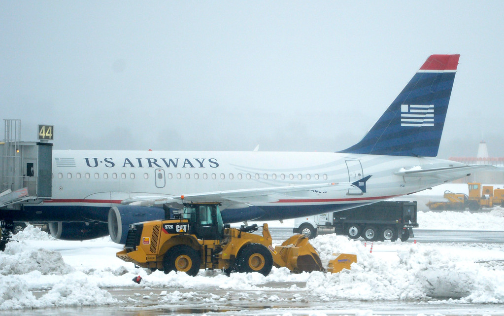 Description of . Planes of US Airways sit at their gates as work crews continue to clear snow from the runways at Reagan National Airport in Arlington, Virginia, USA, 13 February 2014. All flights from Reagan National were grounded as the Washington, DC metropolitan area received over a foot of snow. Heavy winter snowfalls hit large parts of USA from Texas to the East Coast.  EPA/SHAWN THEW