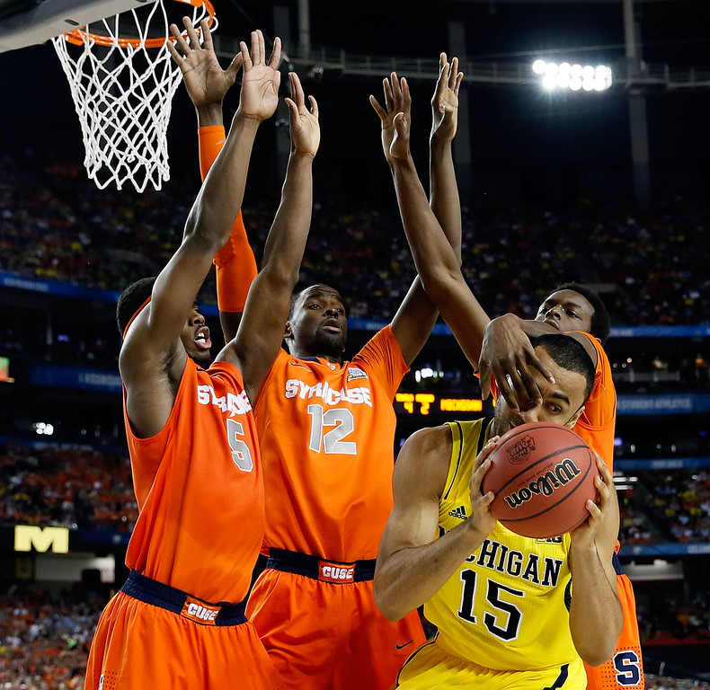 Description of . ATLANTA, GA - APRIL 06:  Jon Horford #15 of the Michigan Wolverines looks to pass the bal as he is defended by C.J. Fair #5, Baye Keita #12 and Jerami Grant #3 of the Syracuse Orange during the 2013 NCAA Men's Final Four Semifinal at the Georgia Dome on April 6, 2013 in Atlanta, Georgia.  (Photo by Kevin C. Cox/Getty Images)