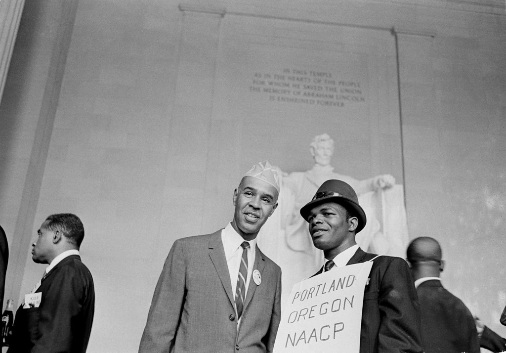 Description of . Jimmy Walker, a marcher in the March On Washington demonstration from Portland, Ore., right, talks to Roy Wilkins, NAACP leader, as they stand in front of the Lincoln statue at the Lincoln Memorial, Aug. 28, 1963.  (AP Photo)