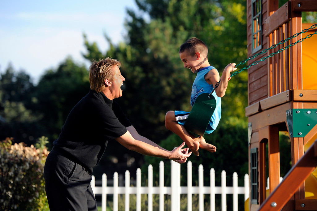 Description of . Lori Moriarty tickles Santos, 5,  while playing on the swing outside their home in Jefferson County, Wednesday, July 11, 2012. Craig F. Walker, The Denver Post