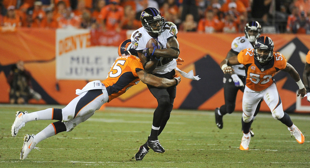 Description of . Denver Broncos cornerback Chris Harris (25) tackles Baltimore Ravens wide receiver Jacoby Jones (12).  (Photo by Tim Rasmussen/The Denver Post)