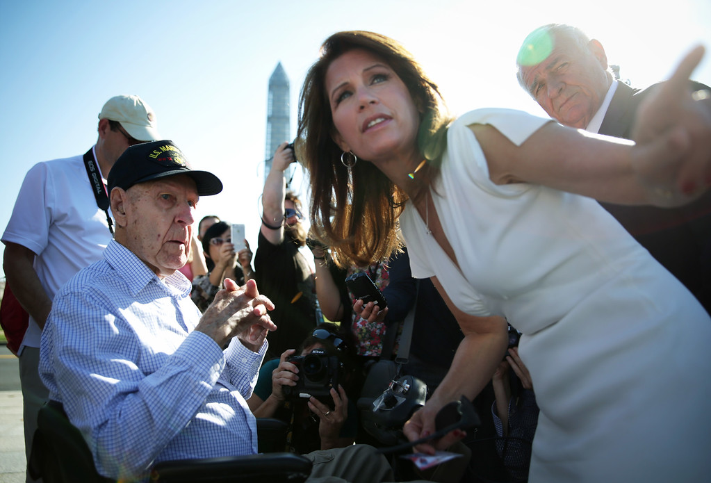 Description of . Ninety-six-year-old World War II veteran Eugene Morgan (L) of West Memphis, Arkansas, listens to U.S. Rep. Michele Bachmann (D-MN) (2nd R) as Rep. John Carter (R-TX) (R) looks on during Morgans visit to the World War II Memorial October 2, 2013 in Washington, DC. Congressional members opened up the barricades of the memorial again and welcomed veteran groups to visit, most of them came on Honor Flights from around the country, on the second day of the government shutdown.  (Photo by Alex Wong/Getty Images)