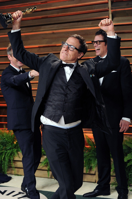 Description of . David O. Russell poses with Spike Jonze's award at the 2014 Vanity Fair Oscar Party, on Sunday, March 2, 2014, in West Hollywood, Calif. (Photo by Evan Agostini/Invision/AP)