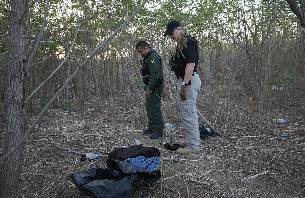Description of . LA JOYA, TX - APRIL 11:  U.S. Customs and Border Protection agents examine efuse left by undocumented immigrants and smugglers on a brush path near the U.S.-Mexico border on April 11, 2013 in La Joya, Texas. According to the U.S. Border Patrol, undocumented immigrant crossings have increased more than 50 percent in Texas\' Rio Grande Valley sector in the last year. Border Patrol agents say they have also seen an additional surge in immigrant traffic since immigration reform negotiations began this year in Washington D.C. Proposed reforms could provide a path to citizenship for many of the estimated 11 million undocumented workers living in the United States.  (Photo by John Moore/Getty Images)