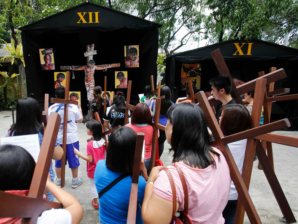 Description of . Catholic devotees carry crosses to one of the Stations of the Cross while doing the